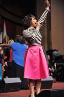 Erica Campbell lifts her hand in praise