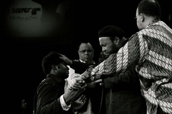 Andrae Crouch prays for Kevin Singleton as Israel and Bishop Garlington agree
